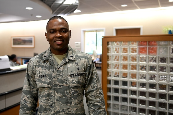 A man in the Airman Battle Uniform smiles at the camera.