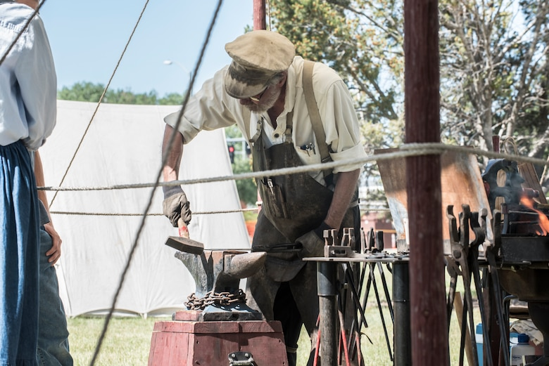 Jan Manning, Fort DA Russell Days volunteer, hammers an 'S' hook into iron for a blacksmith demonstration at F.E. Warren Air Force Base, Wyo., July 19, 2019. These presentations allow visitors to feel like they're taking a trip back to the early days of the base. The annual open house invites the community and visitors to tour the base to learn about its history and its current ICBM deterrence mission. (U.S. Air Force photo by Senior Airman Abbigayle Williams)