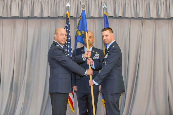 Col. Jeffry Hollman, 412th Mission Support Group commander (left), and new 412th Security Forces Squadron commander, Lt. Col. Joseph Bincarousky, Sr., pose with the squadron's guidon during an assumption of command ceremony in Club Muroc July 19.  (U.S. Air Force photo by Richard Gonzales)