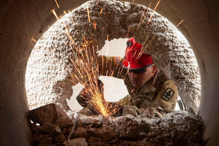 A soldier uses equipment to break through concrete.