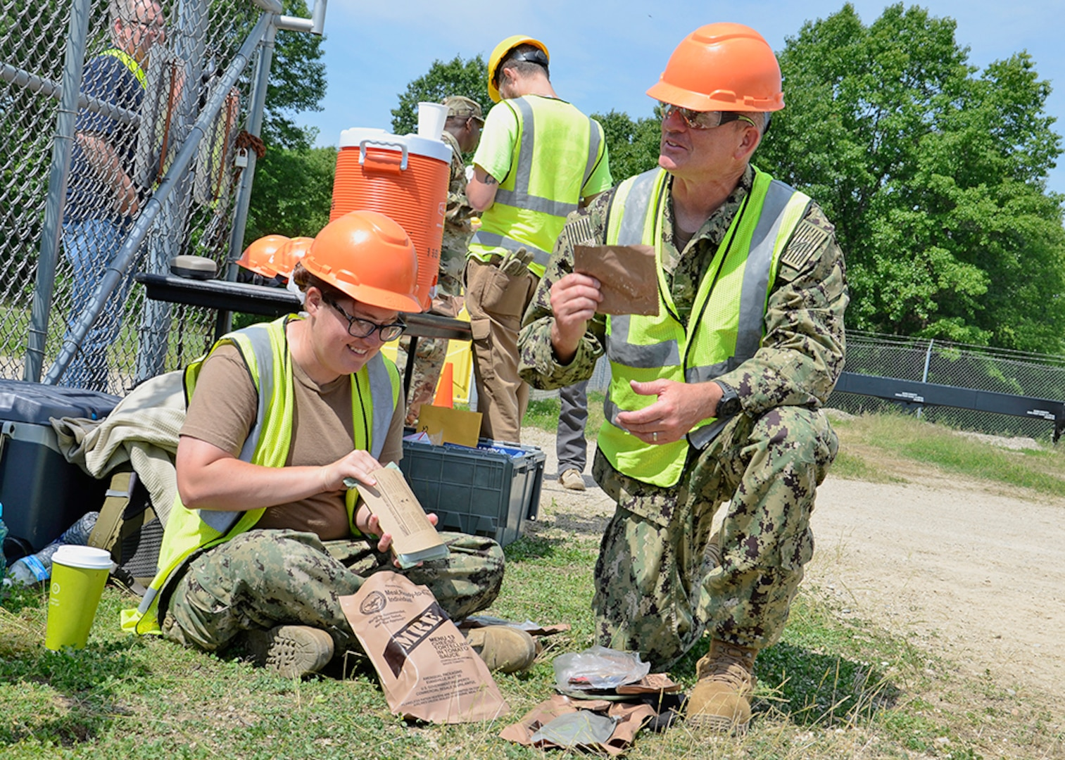 """Navy Petty Officer 3rd Class Stephanie Scholz and Chief Petty Officer David Somerville take a break to enjoy their Meal, Ready-to-Eat, commonly referred to as """"MREs,"""" during OCORT in June."""