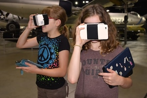Two girls looking through VR goggles