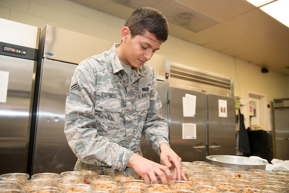 """Airman 1st Class Sebastian Espinosa, 436th Force Support Squadron services journeyman, packages parfaits June 11, 2019, at the Patterson Dining Facility, Dover Air Force Base, Del. The DFAC stays open between meal times, allowing patrons to get """"grab-and-go"""" items, like snacks, salads and prepared sandwiches. (U.S. Air Force photo by Mauricio Campino)"""