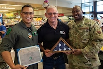 Celebrity Chef Robert Irvine (center) receives an American flag that was flown by the 66th Rescue Squadron on Nellis Air Force Base, Nev., July 19, 2019.