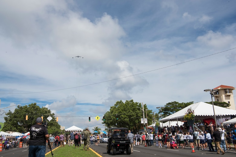 Members of the local community watch a B-52 Stratofortress and two F-15 Eagles fly over Hagatna, Guam during the 75th Liberation Day July 21, 2019.