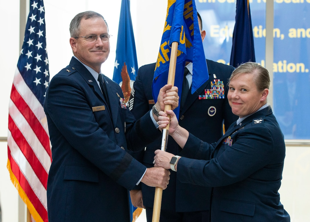 Brig. Gen. James Dienst, 711th Human Performance Wing commander, passes the U.S. Air Force School of Aerospace Medicine flag to Col. Theresa Goodman in a Change of Command ceremony July 19 to symbolize the change of command. (U.S. Air Force photo/Wesley Farnsworth)