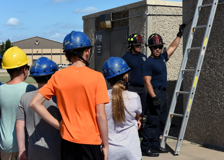 17th Civil Engineering Squadron Firefighters, Trevor Gardner and Frank Villalobos, show the junior firefighters proper ladder operations at the Goodfellow Air Force Base Fire Department on Goodfellow Air Force Base, Texas, July 18, 2019. The children watched a demonstration of ladder safety before ascending and descending in order to put what they learned into action. (U.S. Air Force photo by Airman 1st Class Robyn Hunsinger/Released)