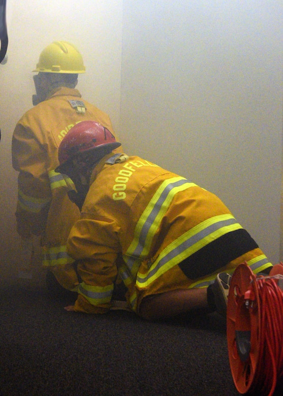Junior firefighters donned in protective gear complete a building search and rescue drill at the Goodfellow Air Force Base Fire Department on Goodfellow Air Force Base, Texas, July 18, 2019. They learned the importance of using a 'buddy system' to ensure that they made it in and out of the simulated environment safely. (U.S. Air Force photo by Airman 1st Class Robyn Hunsinger/Released)