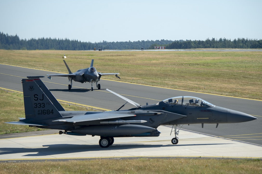 A U.S. Air Force F-35A Lighting II, assigned to the 421st Fighter Squadron, Hill Air Force Base, Utah, and a U.S. Air Force F-15E Strike Eagle, assigned to the 4th Fighter Wing, Seymour Johnson Air Force Base, North Carolina, taxis on the flightline during Operation Rapid Forge at Spangdahlem Air Base, Germany, July 23, 2019. Rapid Forge aircraft are forward deploying to bases in the territory of NATO allies in order to enhance readiness and improve interoperability. (U.S. Air Force photo by Airman 1st Class Branden Rae)