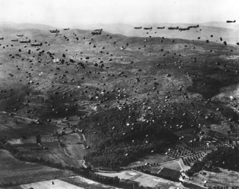 Paratroopers from the 1st Airborne Task Force dropping from Dakotas on one of the three RUGBY drop zones inland while Allied naval landings attacked from the coast seen towards top of picture.