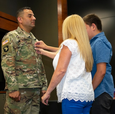 Newly promoted Master Sgt. Erivan Rodriguez's wife, Norma Molina, and son, Yerevan, place his new rank on his uniform during a promotion ceremony.