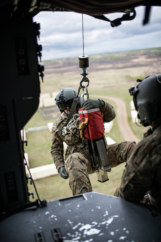 Spc. Patrick Frare, a flight medic with G co. 1-189 AVN, Oregon Army National Guard, prepares to be lowered on a rescue hoist from a HH-60M Blackhawk medevac helicopter Exercise Maple Maple Resolve 19-01 located in Wainwright, AB,  Canada.