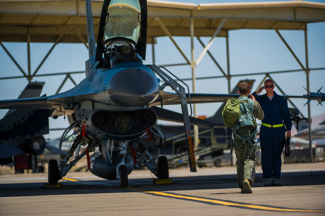 Lt. Col. Jan Stahl, 706th Fighter Squadron commander, renders a salute to Airman 1st Class Russell Lee, 57th Aircraft Maintenance Squadron crew chief July 16, 2019, at Nellis Air Force Base, Nev. Red Flag focuses on the application of core missions to include Command and Control, Intelligence Surveillance, Strike and Personnel Recovery and how to work with Coalition counterparts to ensure success. The 706th Fighter Squadron oversees Air Force Reserve Command members assigned to the U.S. Air Force Warfare Center, supporting missions in its 57th Wing, 53rd Wing and 505th Command and Control Wing. Pilots assigned to the 706 FS fly an array of aircraft to include the F-15C, F-15E, F-16, F-22 and F-35 aircraft. To prepare combat air forces, joint and allied crews with realistic training, pilots in the 706 FS operate with the 64th Aggressor Squadron to facilitate operational threat replication, training, and feedback. The Red Flag exercise will continue through July 26, 2019.