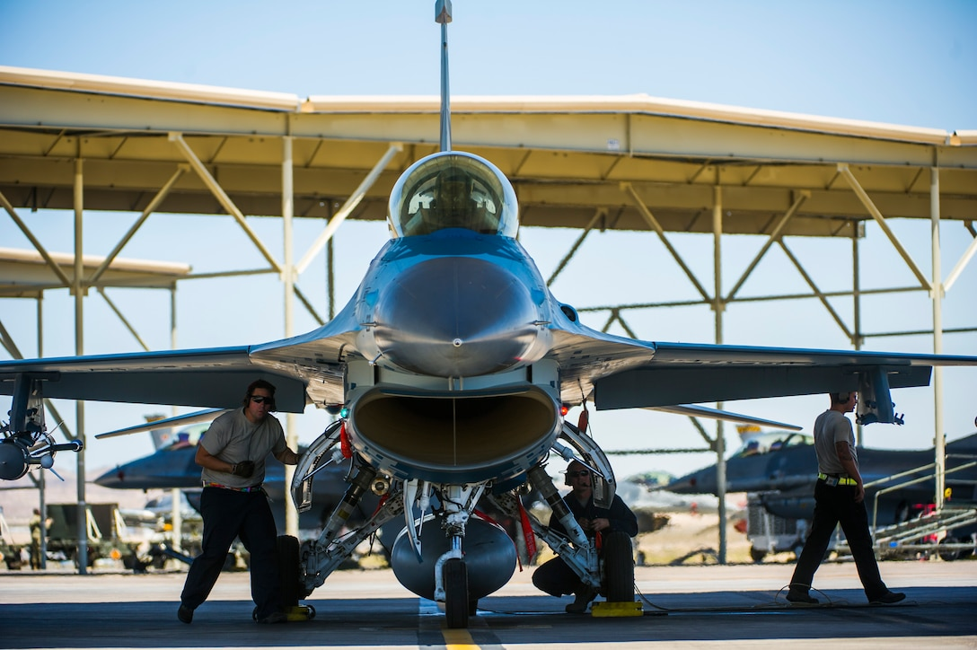 Airmen assigned to the 57th Aircraft Maintenance Squadron crew chief, conduct pre-flight checks on an F-16 fighting falcon assigned to the 64th Aggressors Squadron July 16, 2019, at Nellis Air Force Base, Nev. Red Flag focuses on the application of core missions to include Command and Control, Intelligence Surveillance, Strike and Personnel Recovery and how to work with Coalition counterparts to ensure success. The 706th Fighter Squadron oversees Air Force Reserve Command members assigned to the U.S. Air Force Warfare Center, supporting missions in its 57th Wing, 53rd Wing and 505th Command and Control Wing. Pilots assigned to the 706 FS fly an array of aircraft to include the F-15C, F-15E, F-16, F-22 and F-35 aircraft. To prepare combat air forces, joint and allied crews with realistic training, pilots in the 706 FS operate with the 64th Aggressor Squadron to facilitate operational threat replication, training, and feedback. The Red Flag exercise will continue through July 26, 2019.