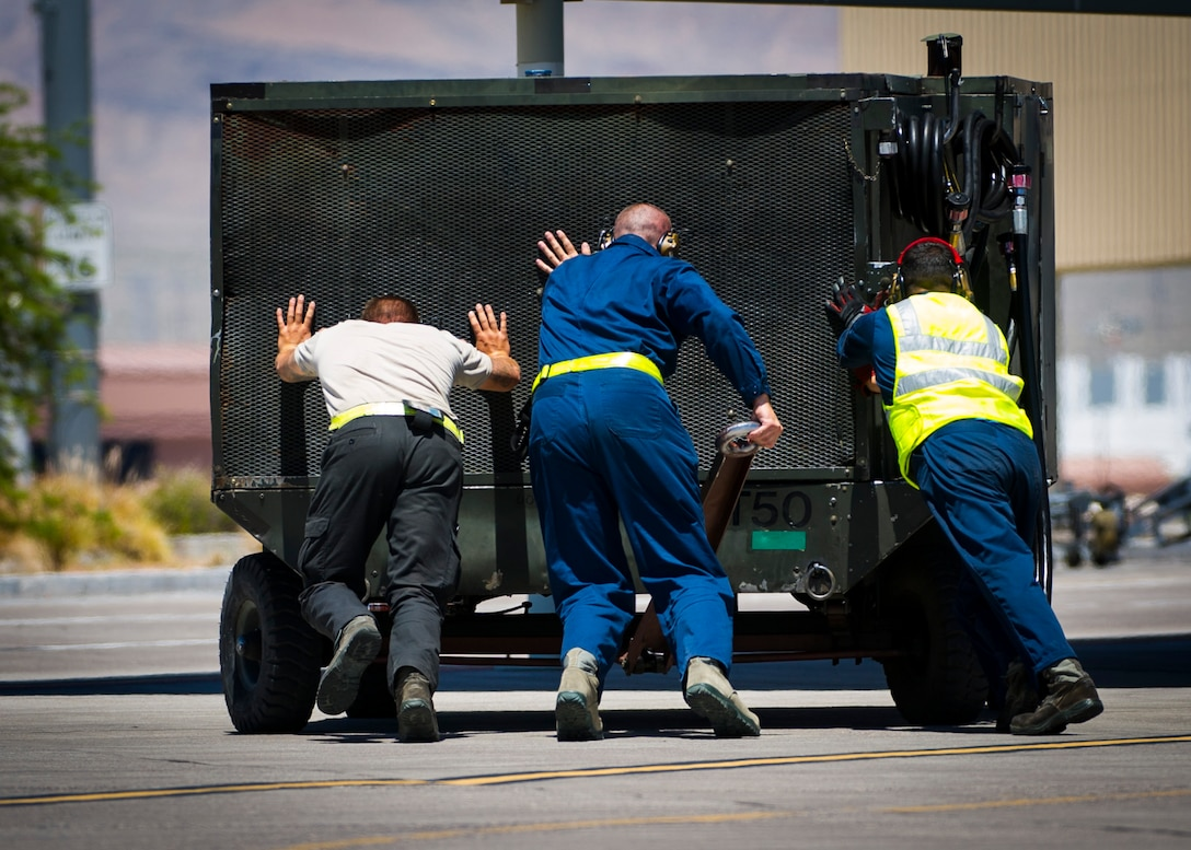 Crew chiefs assigned to the 57th Aircraft Maintenance Squadron push a aircraft hydraulic power supply July 13, 2019, at Nellis Air Force Base, Nev. Red Flag focuses on the application of core missions to include Command and Control, Intelligence Surveillance, Strike and Personnel Recovery and how to work with Coalition counterparts to ensure success. The 706th Fighter Squadron oversees Air Force Reserve Command members assigned to the U.S. Air Force Warfare Center, supporting missions in its 57th Wing, 53rd Wing and 505th Command and Control Wing. Pilots assigned to the 706 FS fly an array of aircraft to include the F-15C, F-15E, F-16, F-22 and F-35 aircraft. To prepare combat air forces, joint and allied crews with realistic training, pilots in the 706 FS operate with the 64th Aggressor Squadron to facilitate operational threat replication, training, and feedback. The Red Flag exercise will continue through July 26, 2019.