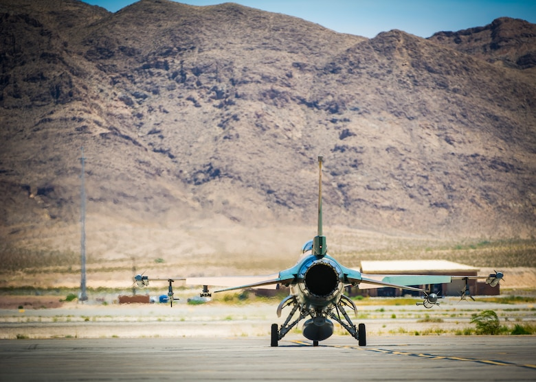 An F-16 fighting falcon assigned to the 64th Aggressors Squadron taxis on the runway July 16, 2019, at Nellis Air Force Base, Nev. Historically, temperatures at Nellis have reached over 118 degrees Fahrenheit. Red Flag focuses on the application of core missions to include Command and Control, Intelligence Surveillance, Strike and Personnel Recovery and how to work with Coalition counterparts to ensure success. The 706th Fighter Squadron oversees Air Force Reserve Command members assigned to the U.S. Air Force Warfare Center, supporting missions in its 57th Wing, 53rd Wing and 505th Command and Control Wing. Pilots assigned to the 706 FS fly an array of aircraft to include the F-15C, F-15E, F-16, F-22 and F-35 aircraft. To prepare combat air forces, joint and allied crews with realistic training, pilots in the 706 FS operate with the 64th Aggressor Squadron to facilitate operational threat replication, training, and feedback. The Red Flag exercise will continue through July 26, 2019.