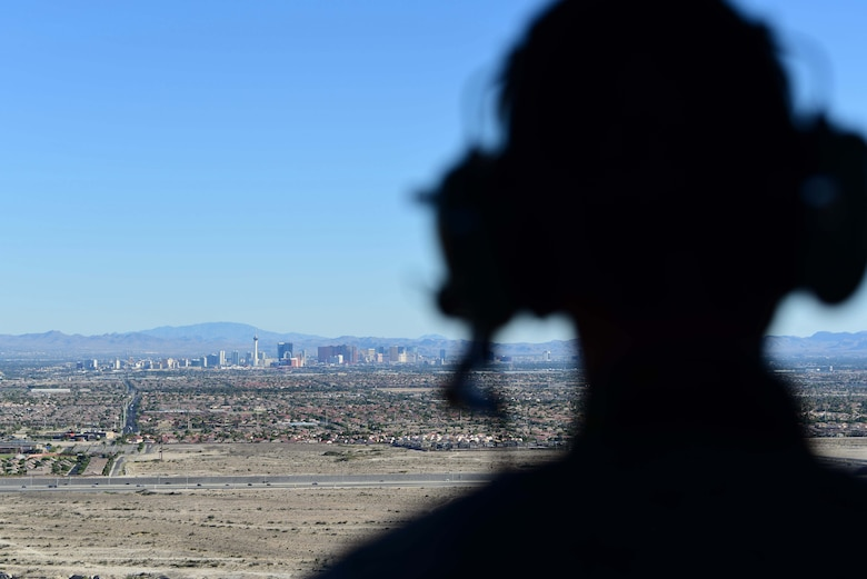 Airman 1st Class William Rosado, 432nd Wing/432nd Air Expeditionary Wing photojournalist, looks out at the Las Vegas skyline from a 66th Rescue Squadron HH-60G Pave Hawk, July 15, 2019. Aircrew with the 66th RS conducted training exercises on the Nevada Test and Training Range and integrated with MQ-9 Reaper aircrew to document the Reaper in flight. (U.S. Air Force photo by Senior Airman Haley Stevens)