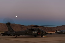 Airmen perform post-flight checks on an HH-60G Pave Hawk at Nellis Air Force Base, Nevada, July 15, 2019. The Pave Hawk is a highly modified version of the Army Black Hawk helicopter and its aircrews support day or night recovery operations in hostile environments. (U.S. Air Force photo by Senior Airman Haley Stevens)