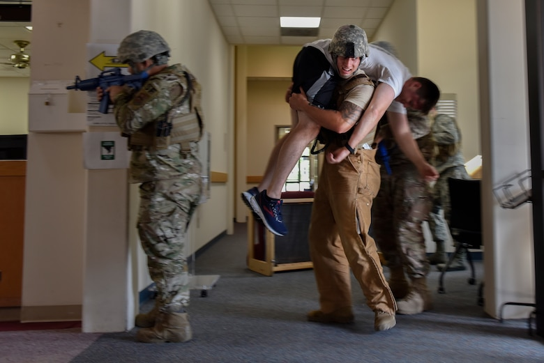 Staff Sgt. Dakota Farrow, 47th Security Forces Squadron military working dog handler, evacuates a simulated active shooter victim during a training exercise at Laughlin Air Force Base, Texas, July 22, 2019. The exercise, aimed at bolstering crisis readiness and response capabilities, simulated a hostage situation that lasted for nearly two hours. (U.S. Air Force photo by Staff Sgt. Benjamin N. Valmoja)