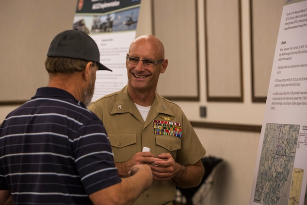 Col. David A. Suggs, the commanding officer of Marine Corps Air Station (MCAS) Yuma, and several base personnel interact with members of the local Yuma community during the Air Installations Compatible Use Zones (AICUZ) Open House at the Pivot Point Conference Center in Yuma, Ariz., July 17, 2019. The Department of Defense established the AICUZ program to assist local governments and communities in identifying and planning for compatible land use and development in the vecinity of military air installations. The primary functions of the AICUZ study is to present noise contours and accident potential zones for an airfield. (U.S. Marine Corps photo by Sgt. Isaac D. Martinez)