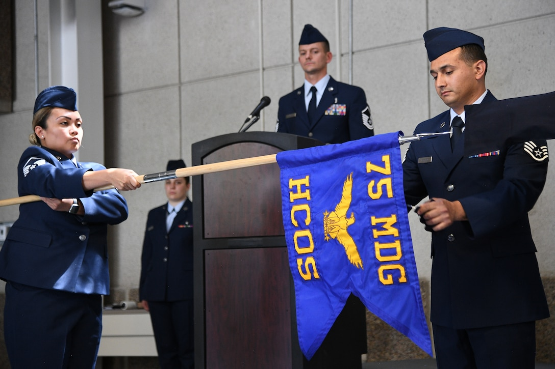 Staff Sgt. Nephi Marsten, a mental health technician, unfurls the 75th Health Care Operations Squadron guidon during an inactivation and redesignation ceremony July 16, 2019, at Hill Air Force Base, Utah. The 75th Medical Operations Squadron was inactivated and redesignated as the 75th Health Care Operations Squadron. The change is part of an Air Force initiative to improve patient care and military readiness. (U.S. Air Force photo by R. Nial Bradshaw)