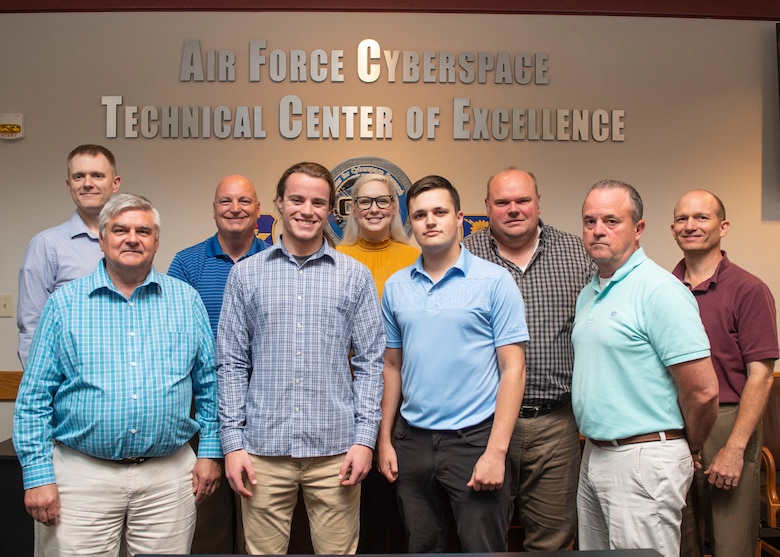 Back left, Air Force Institute of Technology Assistant Professor of Cyber Systems Mark Reith, second from right, Matthew Dever, Air Force Cyberspace Technical Center of Excellence, assistant to the director, and Reith's graduate students, created a cloud based educational hub as a research project to improve user motivation and engagement with training. (U.S. Air Force photo/Wes Farnsworth)