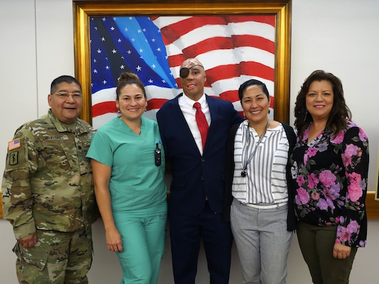 Retired Sgt. Mario Lopez poses for a photo with Brooke Army Medical Center staff members after his painting of the American flag is unveiled in the Medical Mall of the hospital at Joint Base San Antonio-Fort Sam Houston. Lopez, a former BAMC patient who was severely injured in an IED attack in Afghanistan in 2008, learned to use painting therapeutically to help him overcome an array of challenges he has faced over the past decade. The painting was donated to BAMC by former United Nations Ambassador Warren W. Tichenor.