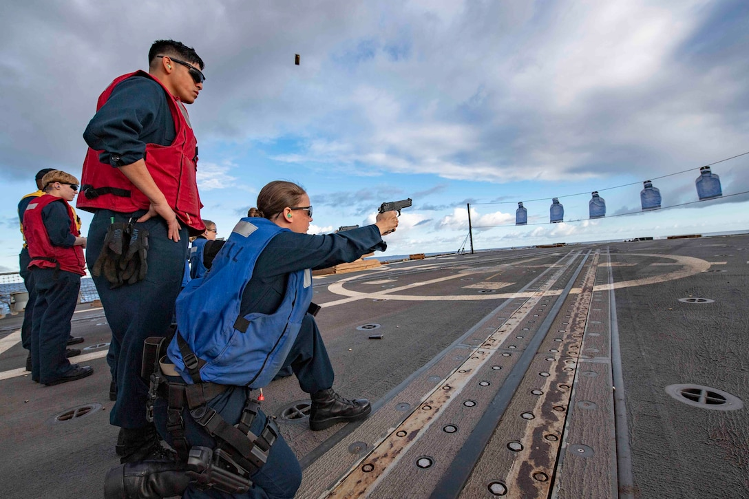 A sailor fires a handgun at targets on a ship's deck while two others observe.