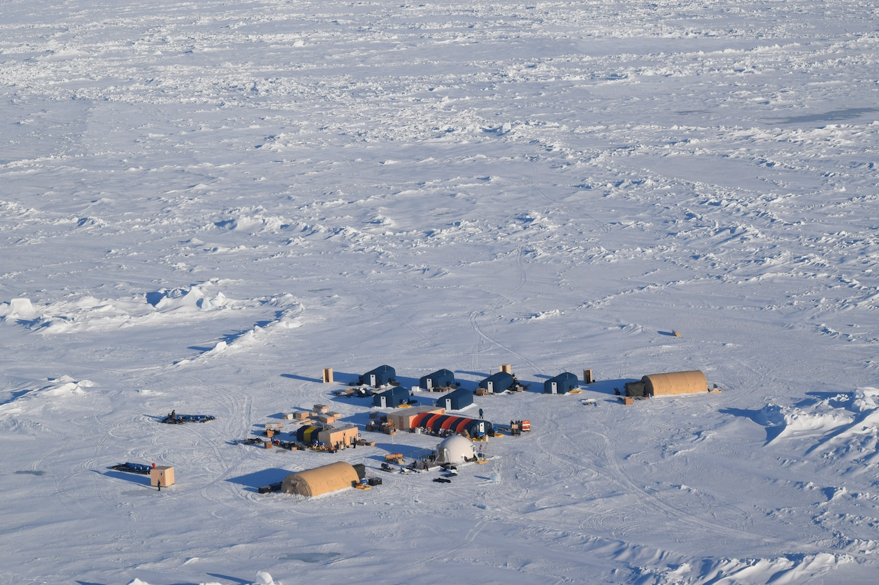 A tiny military camp is surrounded by a vast expanse of snow.
