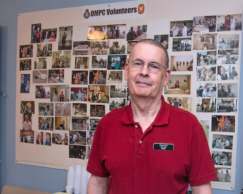 Phil Lewis, Brooke Army Medical Center volunteer since 1996, stands in front of a photo collage of the Department of Ministry & Pastoral Care volunteer office April 16.