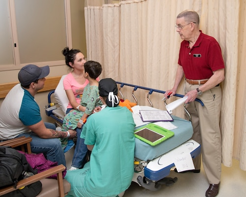 Phillip Lewis (right), on-call chaplain and post anesthesia care unit volunteer, talks with a family in the Post Anesthesia Care Unit at Brooke Army Medical Center, while Air Force Maj. Katherine M. Slogic, pediatric anesthesiologist, listens to the patient's lungs April 16.