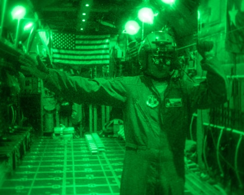 An Airman provides direction via hand gestures to assist loading cargo to a C-130.