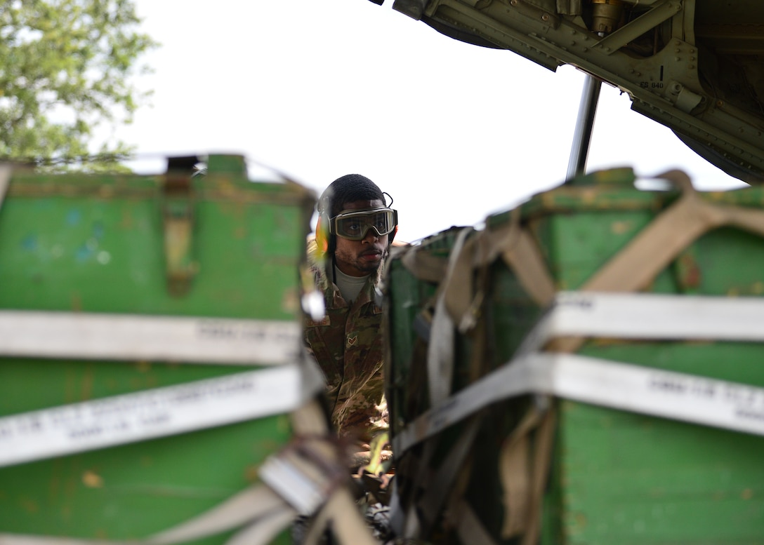 U.S. Air Force Senior Airman Kenneth Saunders, 435th Contingency Response Squadron mobile aerial porter, examines a pallet at Powidz Air Base, Poland, July 13, 2019. As a mobile aerial porter, Saunders assisted in teaching new processes and techniques to his Polish counterparts during Aviation Rotation 19-3. (U.S. Air Force photo by Staff Sgt. Jimmie D. Pike)