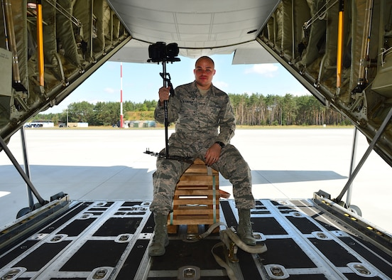 U.S. Air Force Staff Sgt. Devin Nothstine, 86th Airlift Wing Public Affairs broadcast journalist, shows off his equipment prior to takeoff from Powidz Air Base, Poland, July 11, 2019. As a member of public affairs and a broadcaster, Nothstine was responsible for documenting operations, creating and distributing videos, and working with media outlets to highlight U.S. and Polish efforts during Aviation Rotation 19-3. (U.S. Air Force photo by Staff Sgt. Jimmie D. Pike)