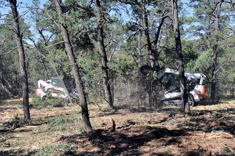 Two members of the Kirtland's Wildland Support Module use skid steer loaders to masticate overgrowth in the eastern-most remote forest area of Kirtland Air Force Base, N.M., July 18, 2019. The team of six wildland firefighters have thinned out 70 acres of forest expanding on the initial fuel breaks that were created since the project broke ground in spring of 2019.  (U.S. Air Force photo by Staff Sgt. Dylan Nuckolls)