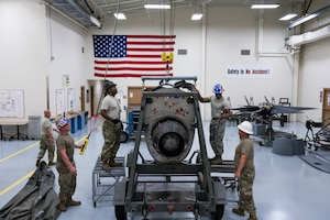 "Master Sgt. Donald Maloid, 403rd Aircraft Maintenance Squadron aerospace propulsion supervisor (black helmet) and crew, watches the crane winch lowered on an engine July 14, 2019 at Keesler Air Force Base, Mississippi. The ""prop"" shop is responsible for the blades as well as the nearly one ton engines they're attached to. (U.S. Air Force photo by Tech. Sgt. Christopher Carranza)"