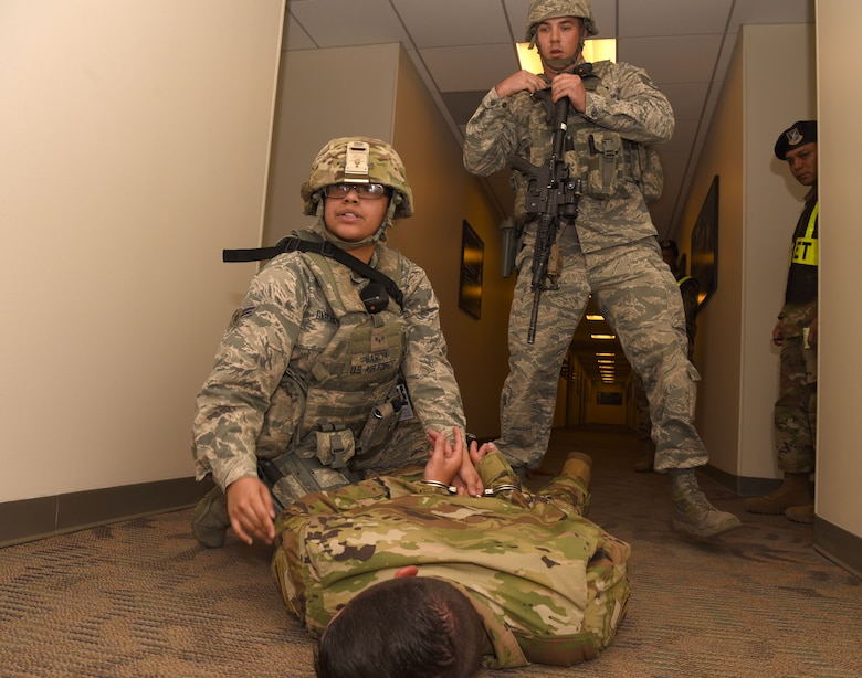 SCHRIEVER AIR FORCE BASE, Colo.--Airman 1st Class Aurelis Garcia, 50th Security Forces Squadron response force member, left, and Staff Sgt. Clifton Cole, 50th SFS response force leader, apprehend a suspect in a simulated active shooter incident during a field training exercise at Schriever Air Force Base, Colorado, July 20, 2019. The squadron conducted the exercise as part of the 50th Space Wing's continued commitment to base readiness. (U.S. Air Force photo by Staff Sgt. Matthew Coleman-Foster)