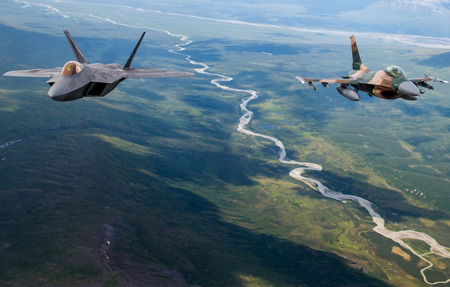 A U.S. Air Force F-22 Raptor from Joint Base Elmendorf-Richardson and an F-16 Fighting Falcon from Eielson Air Force Base fly in formation over the Joint Pacific Alaska Range Complex, July 18, 2019.