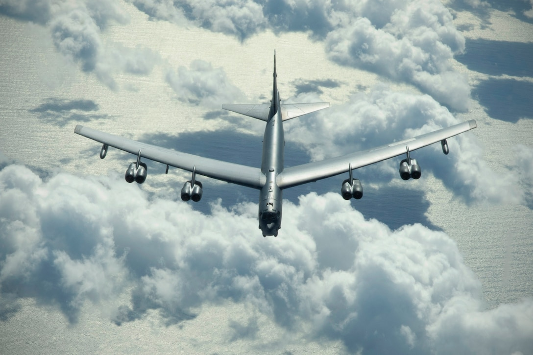 A large aircraft flies above clouds and the ocean.