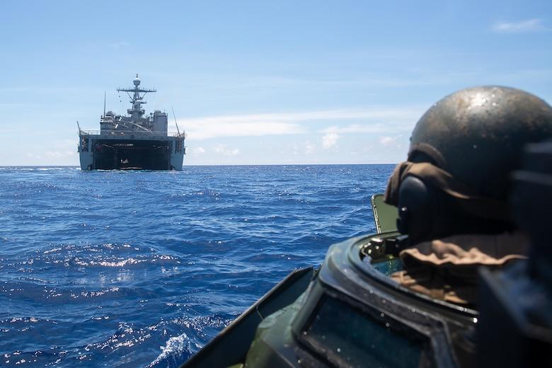 An amphibious assault vehicle approaches a ship.