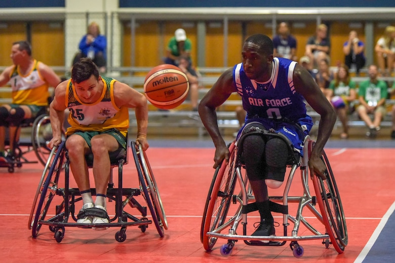 U.S. Air Force Staff Sgt. Kevin Greene, Team Air Force, and Australian Army veteran Private Rye Shawcroft, Team Australia, hustle for a ball during the 2019 DoD Warrior Games wheelchair basketball tournament in the Tampa Convention Center, June 25, 2019. The Warrior Games were established in 2010 as a way to enhance the recovery and rehabilitation of wounded, ill and injured service members and expose them to adaptive sports. Approximately 300 athletes are participating in 13 adaptive sport competitions June 21-30. The athletes represent the United States Army, Marine Corps, Navy, Air Force and Special Operations Command. Athletes from the United Kingdom, Australia, Canada, the Netherlands, and Denmark will also compete. (DoD photo by Staff Sgt. Vito T. Bryant)