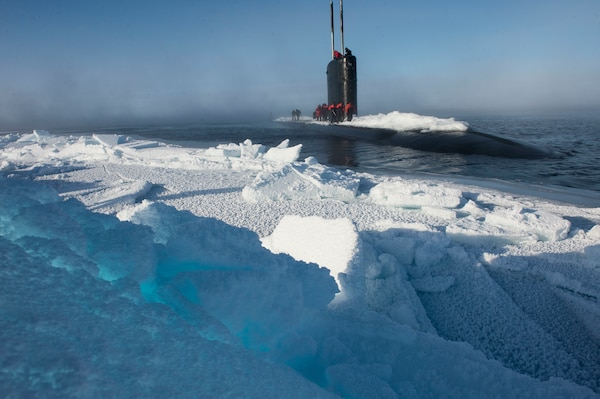A submarine is surfaced near a large sheet of ice. Snow is piled up on top of the submarine.