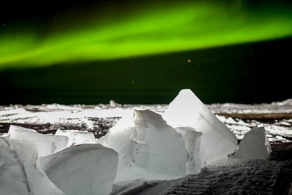 Eerie green lights streak across a dark sky.