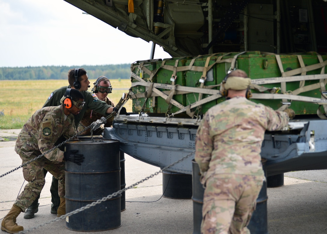U.S. Air Force Airmen deployed to Powidz Air Base, Poland, perform a combat offload bravo July 20, 2019. Method bravo requires the use of barrels to set the pallets on and is used when aircraft loaders are unavailable at a destination. (U.S. Air Force photo by Staff Sgt. Jimmie D. Pike)