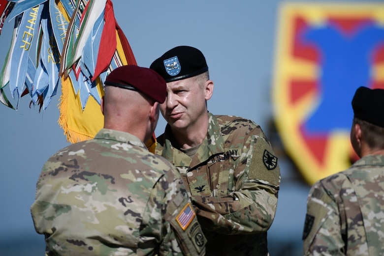 U.S. Army Col. Timothy Zetterwall, incoming 7th Transportation Brigade (Expeditionary) commander, receives the colors from Maj. Gen. Brian J. McKiernan, XVIII Airborne Corps and Fort Bragg deputy commanding general, during a change of command ceremony at Joint Base Langley-Eustis, Virginia, July 18, 2019.