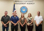 Group photo of male and female employees in front of the American flag and the DCMA seal