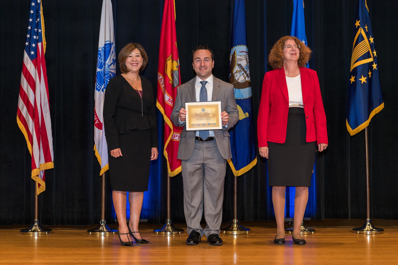 3 individuals pose with one in center holding diploma