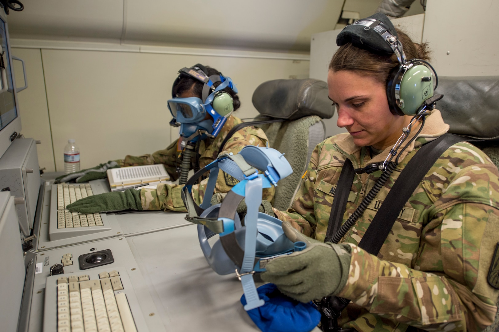 Army airborne technician systems specialist (right) and deputy mission control commander, both with Army JSTARS, participate in emergency drill onboard E-8C Joint STARS during routine training mission at Robins Air Force Base, Georgia, March 21, 2019 (U.S. Air National Guard/Nancy Goldberger)