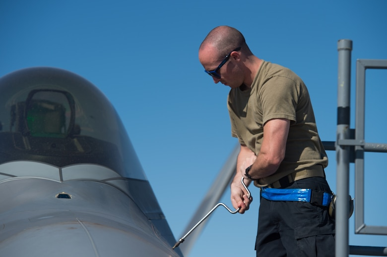 U.S. Air Force Airman 1st Class Dylan Brown, 94th Aircraft Maintenance Unit integrated avionics journeyman, reattaches a panel after performing maintenance on an F-22 Raptor at Nellis Air Force Base, Nevada, July 16, 2019.