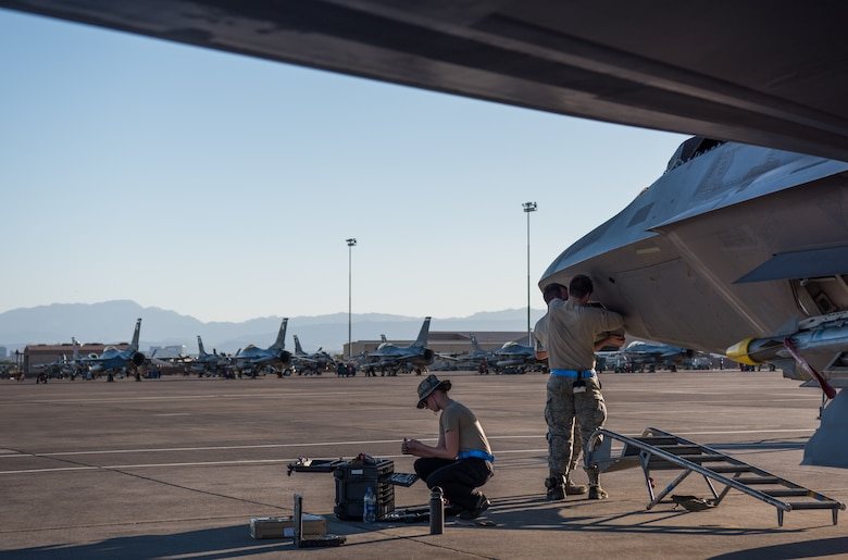 U.S. Air Force integrated avionics specialists from 94th Aircraft Maintenance Unit perform maintenance on an F-22 Raptor at Nellis Air Force Base, Nevada, July 16, 2019.